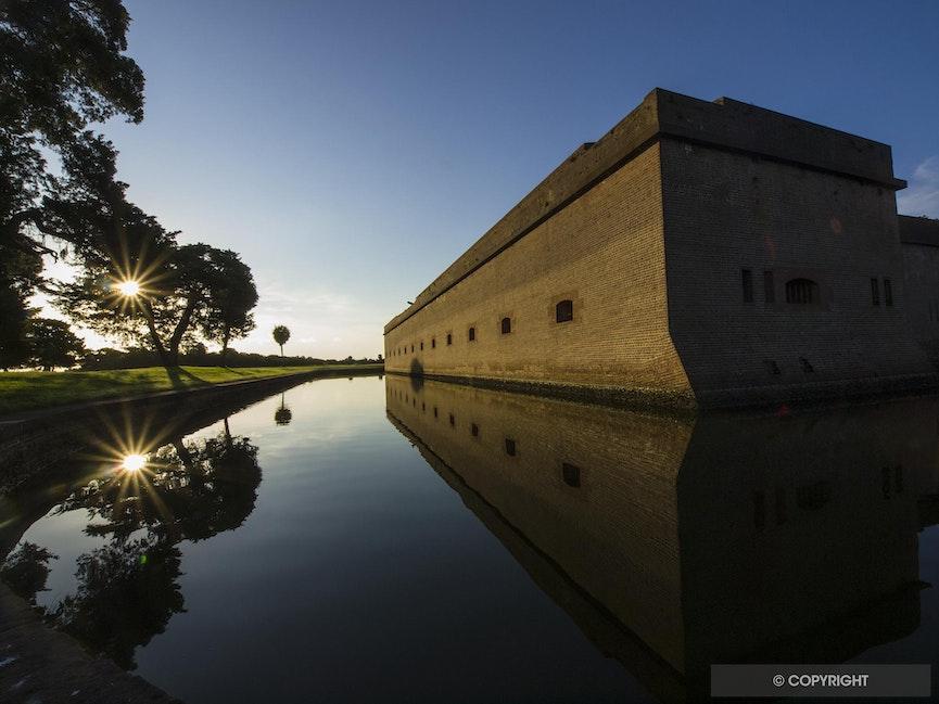 Moat Sunrise - Starburst in moat reflects sunrise in Fort Pulaski National Monument, Georgia.